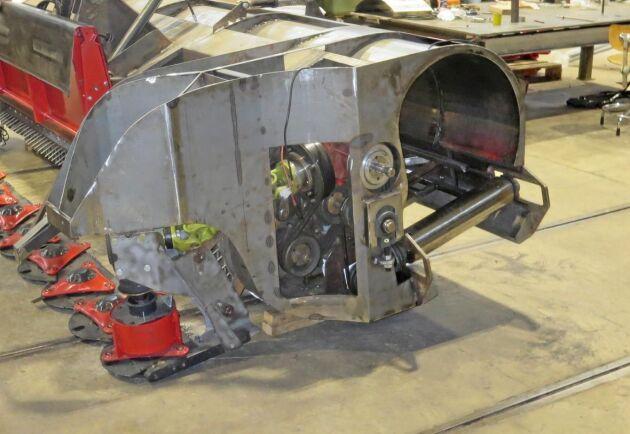 Prototyp 2 till Multiflow har en höj- och sänkbar rotorslåtterbalk och bakom den en fingerrotorpickupp som lyfter grönmassan in i maskinen eller bredsprider den på stubben bakom maskinen, här sedd från sidan som vetter mot mitten av maskinen.