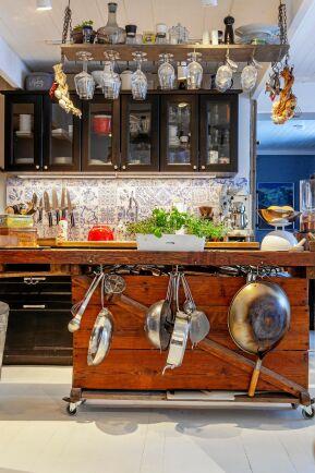 Arbetsbänken i köket är en gammal snickarbänk som är fin mot det blåvitmönstrade kaklet.