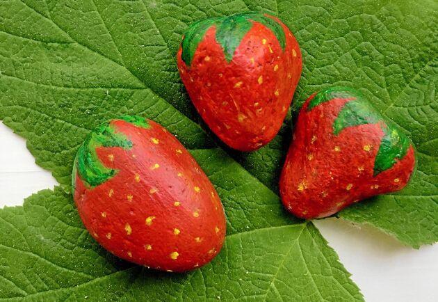 Med stenar målade som jordgubbar kan du få ha de riktiga i fred. En trast kommer hoppande i jordgubbslandet, på väg att hacka i sig en saftig gubbe.