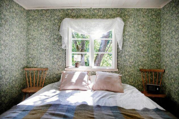 Ljuset dansar genom det gamla fönsterglasets och sprider ljus över den grönblommiga Lilla Dockekulla-tapeten.