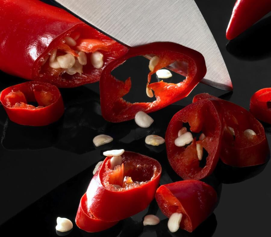 detail of cutting red chili slices with big blade in dark reflective back