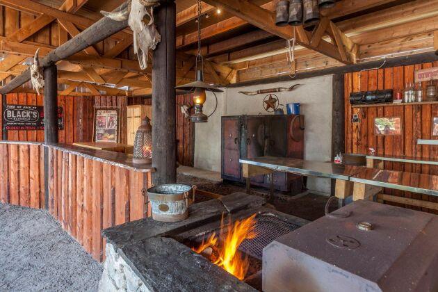 Barbequekök under tak med grill och rökar i bakgrunden