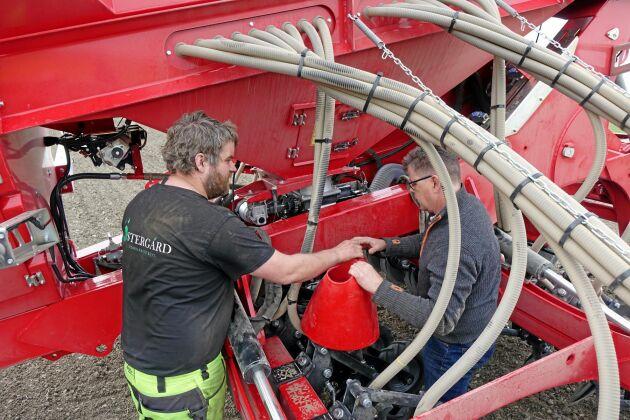 Johan Olsson och Lars Nilsson kollar hur många havrefrön som kommer ut ur såmaskinen Weaving GD 6001T.