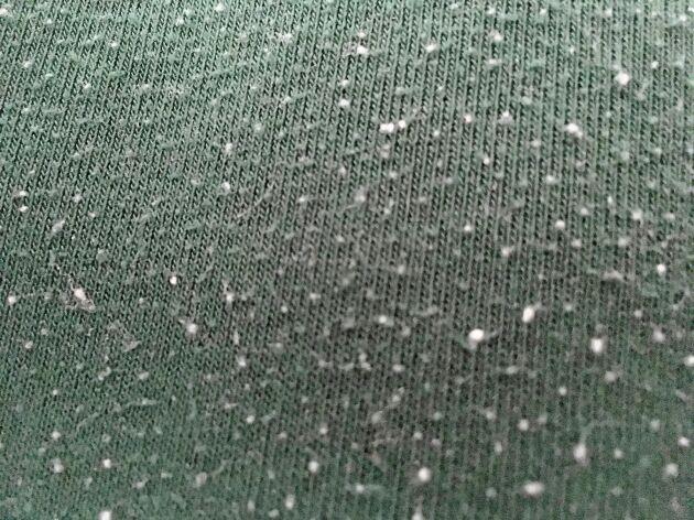 En noppig tröja har blivit luddad. Vita fibrer har fastnat i det gröna och gjort ont värre.