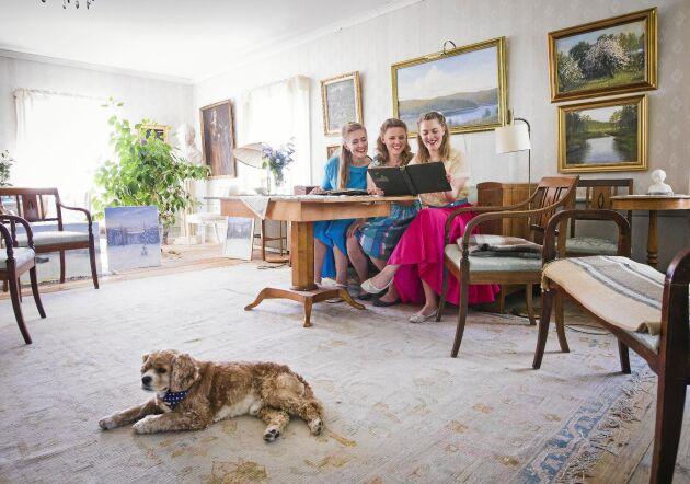 Salongen i huvudbyggnaden sträcker sig över halva övervåningen. Den är full av minnen av tidigare generationen, som det fotoalbumet som Emelie, Josefine och Maria tittar i. Hunden Bobby i förgrunden.