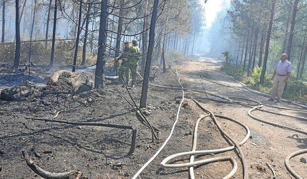 Hemvärnet försöker bekämpa elden. Markägaren Jan Oscarsson kan bara se på.