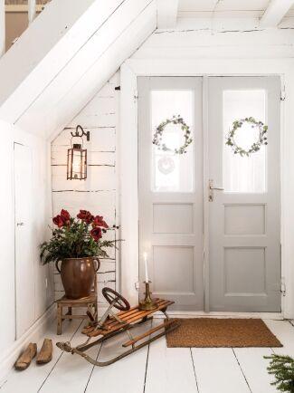 Timmerväggar ger hallen en mjukt rustik känsla och är en bra fond till de gamla trämöblerna.