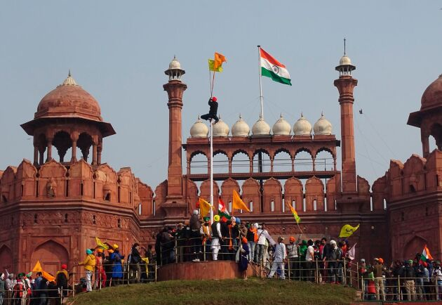 Demonstranter har forcerat polisens avspärrningar och tagit sig upp på det historiska röda fortet i New Delhi.