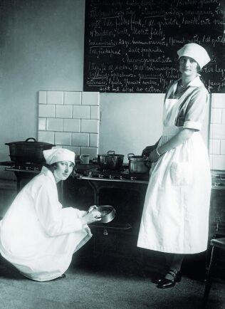 1920-tal. Kronprinsessan Märtha och hennes syster Astrid i ett kök med recept på en stor tavla ovanför spisen.