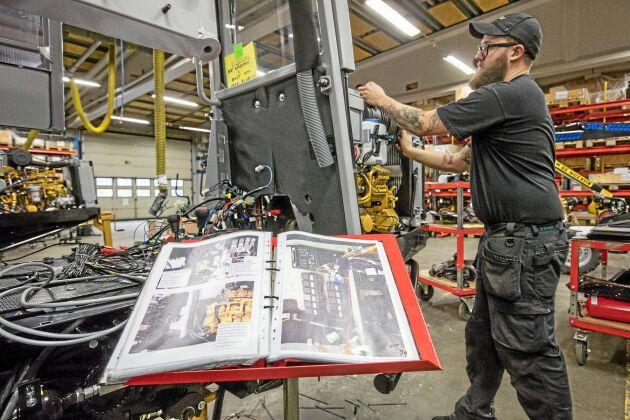 Byggmanualen har montörerna själv gjort. Det är en ständigt pågående process att hitta det bästa sättet att bygga ihop maskinerna. Kaj Fjällström monterar delar i motorrummet och byggmanualen syns i förgrunden.