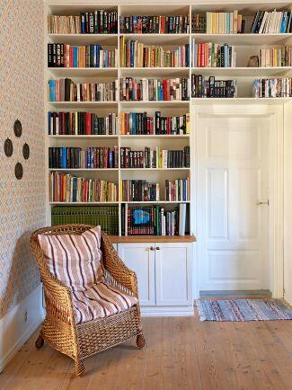 Arbetsrummet har platsbygga bokhyllor, fyllda med böcker från golv till tak. Nederst finns praktiska skåp där man kan stänga in saker som behövs men inte är så fina att se på.