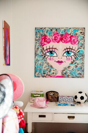 På väggarna sitter Toves färgglada målningar.