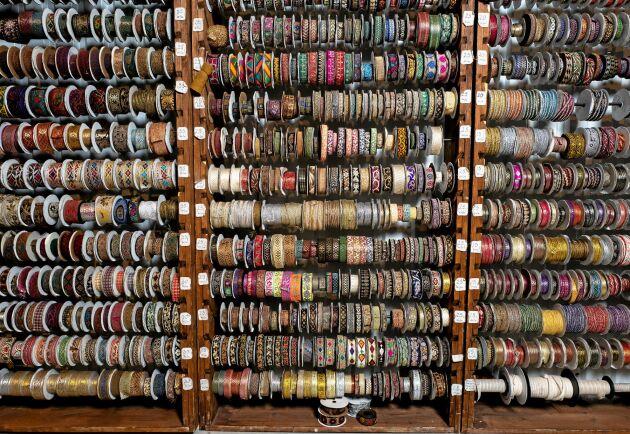Skattgömma. En hel vägg full med broderade och mönstrade band i glänsande material.